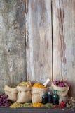 Het helen van kruiden in jutezakken op oude houten achtergrond Stock Foto's