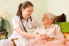Het helpen van een zieke bejaarde Stock Foto's