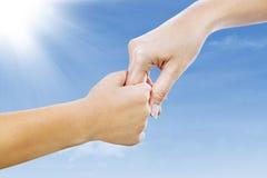 Het helpen van hand onder blauwe hemel Stock Afbeelding