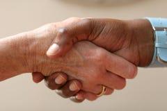 Het helpen van hand schudt een andere in een overeenkomst royalty-vrije stock afbeeldingen