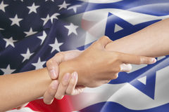 Het helpen van handen met de Amerikaanse en vlaggen van Israël stock afbeelding