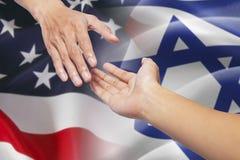 Het helpen van handen met de Amerikaanse vlaggen van Israël en stock foto's