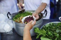 Het helpen van Mensen met Honger met Vriendelijkheid: het concept het levensproblemen, honger in de maatschappij: concept het voe stock foto