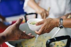 Het helpen van Mensen met Honger met Vriendelijkheid: het concept het levensproblemen, honger in de maatschappij: concept het voe stock fotografie