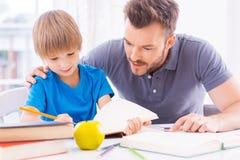 Het helpen van zoon met thuiswerk Stock Foto
