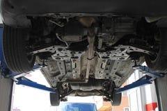 Het herstellen van een auto in een autoreparatiewerkplaats Stock Afbeelding