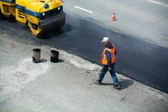 Het herstellen van wegsgedeelte Arbeider in oranje vest stock afbeelding