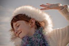 Het het formaatbeeld van het kleurenlandschap van jong rood haired meisje die Eskimo gestileerd bont dragen maakte kap in orde Royalty-vrije Stock Foto's