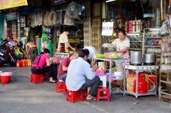 Het het Vietnamese fruit en voedsel van de mensenverkoop bij winkel op straat dichtbij Ben Stock Foto