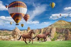 Het hete lucht ballooning en twee paarden die in Cappadocia, Turkije lopen stock fotografie