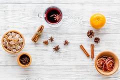 Het hete overwogen wijn of grog koken voor nieuwe jaarviering met sinaasappelen en kruideningrediënten op lichte vlakke achtergro royalty-vrije stock foto