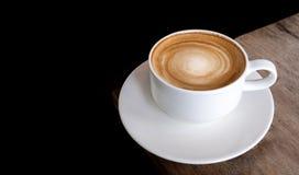 Het hete spiraalvormige schuim van de koffiecappuccino op houten lijst aangaande zwarte backg Royalty-vrije Stock Foto's