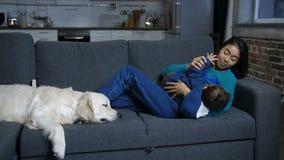 Het Hindoese mamma en zuigelings ontspannen op bank met hond stock video