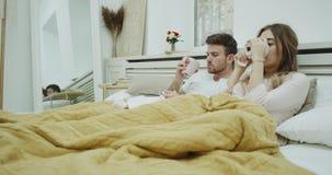 Het hoestende paar in bed heeft een slechte griep, voelend soozieken die sommige hete dranken drinken en onder een warme deken be stock video