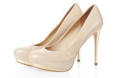 Het hoge paar van hiel beige schoenen op wit stock foto's