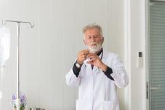 Het hogere artsenmannetje bereidt het geven van vaccin met injectie of spuit aan doen schrikken patiënt bij het ziekenhuis voor royalty-vrije stock foto