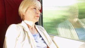 Het hogere blonde vrouw ontspannen in hoge snelheids internationale trein Zeer hoge snelheid Het lichte natuurlijke schudden stock videobeelden