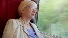 Het hogere blonde vrouw ontspannen in hoge snelheids internationale trein Zeer hoge snelheid Het lichte natuurlijke schudden stock video