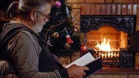 Het hogere boek van de mensenlezing dichtbij de open haard en Kerstboom bij Kerstmisvooravond Stock Afbeeldingen