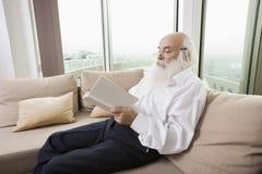 Het hogere boek van de mensenlezing op bank binnenshuis Royalty-vrije Stock Foto's