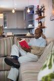 Het hogere boek van de mensenlezing terwijl het zitten op bank Stock Foto