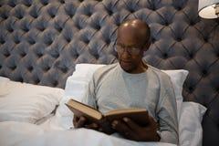 Het hogere boek van de mensenlezing terwijl het zitten in slaapkamer Royalty-vrije Stock Fotografie