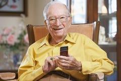 Het hogere mens texting op mobiele telefoon Stock Foto