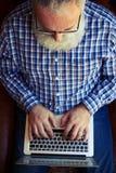 Het hogere mens typen op laptop Stock Foto's