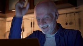 Het hogere mensenwerk aangaande laptop van huisbureau bij nacht De zakenman ontvangt goed opgewekt en gelukkig nieuws stock videobeelden