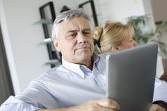 Het hogere nieuws van de mensenlezing op tablet Royalty-vrije Stock Foto's
