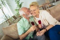 Het hogere paar die zich in nieuw huis bewegen die bij elkaar glimlachen en drinkt wijn stock foto