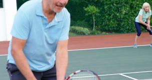 Het hogere paar geven klopt tot elkaar terwijl het spelen van tennis 4k stock videobeelden