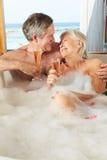 Het hogere Paar Ontspannen in Bad die Champagne Together drinken Stock Afbeelding