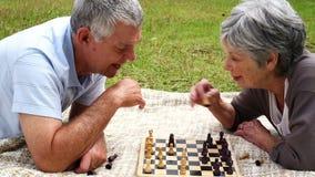 Het hogere paar ontspannen in het park die op een algemeen het spelen schaak liggen stock video