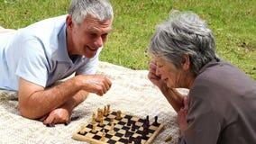 Het hogere paar ontspannen in het park die op een algemeen het spelen schaak liggen stock footage