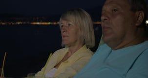 Het hogere paar ontspannen met cocktails op strand bij nacht stock videobeelden