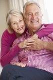 Het hogere Paar Ontspannen op Sofa Together At Home Stock Fotografie