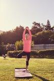 Het hogere uitrekken zich in een in evenwicht brengende yoga stelt in openlucht Stock Foto's