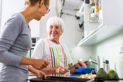 Het hogere vrouw/grootmoeder koken in een moderne ondiepe keuken  stock fotografie