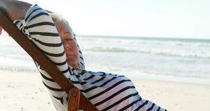 Het hogere vrouw ontspannen op sunlounger bij strand stock videobeelden