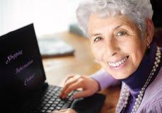 Het hogere vrouw typen op laptop Stock Afbeeldingen