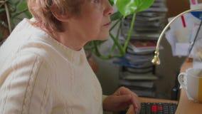 Het hogere vrouw typen op toetsenbord, het werkruimte, profiel, handen stock video