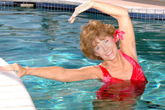 Het hogere vrouw uitrekken zich in de pool Stock Foto