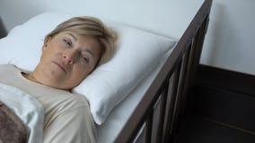 Het hogere vrouw wekken na chirurgieverrichting, die in het ziekenhuisbed liggen, gezondheid stock video