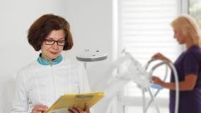 Het hogere vrouwelijke arts tonen beduimelt omhoog het stellen bij het ziekenhuis stock footage
