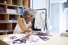 Het hogere vrouwelijke media creatieve werken aan tijdschriftlay-out royalty-vrije stock afbeelding