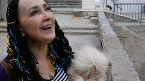 Het hogere vrouwen Kaukasische behoren tot een bepaald ras houdt haar hond in haar wapens - witte Pekinees stock videobeelden