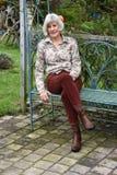 Het hogere wonan ontspannen in haar tuin stock foto's