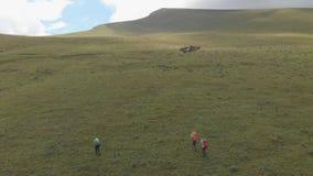 Het hommelschot van een groep toeristen beklimt de berg stock footage