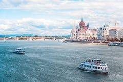 Het Hongaarse Parlement builded op de rivieroever van de Donau, waarop de schipzeilen stock foto